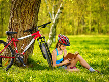 Bikes cycling girl wearing helmet read book on rest near bicycle. Royalty Free Stock Photo