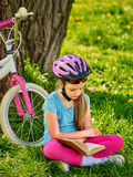 Bikes cycling girl wearing helmet reads book. Royalty Free Stock Images