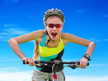 Bikes cycling girl wearing helmet rides bicycle aganist blue sky. Royalty Free Stock Images