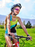 Bikes cycling girl wearing helmet rides bicycle aganist blue sky. Stock Photography