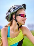 Bikes cycling girl wearing helmet rides bicycle aganist blue sky. Stock Images