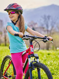 Bikes cycling girl wearing helmet rides bicycle. Royalty Free Stock Photography
