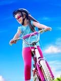 Bikes cycling girl wearing helmet rides bicycle. Stock Image