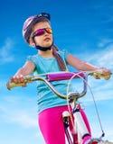 Bikes cycling girl wearing helmet rides bicycle. Royalty Free Stock Image
