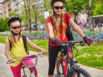 Bikes cycling girls with rucksack on bike lane. Royalty Free Stock Photography