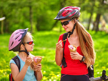 Bikes cycling girls with rucksack cycling eating ice cream cone in summer park. Bikes bicyclist girl. Girls wearing bicycle helmet  with rucksack on back rides Royalty Free Stock Photo