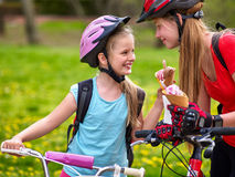 Bikes cycling girls with rucksack cycling eating ice cream cone in summer park. Bikes bicyclist girl. Girls wearing bicycle helmet and gloves with rucksack Stock Photo