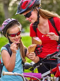 Bikes cycling girls with rucksack cycling eating ice cream cone in summer park. Bikes bicyclist girl. Girls wearing bicycle helmet with rucksack rides bicycle Stock Photos