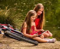 Bikes cycling kids. Girl recreation near bicycle into park. Children watch tablet pc. Girl in ecotourism. Older sister shows younger new game on pc tablet Stock Image
