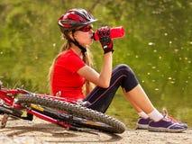 Bikes el casco que lleva de ciclo de la muchacha Consumición de ciclo de la muchacha del agua de botella Imágenes de archivo libres de regalías