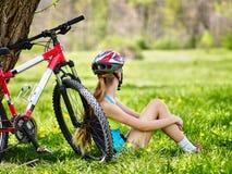 Bikes el casco que lleva de ciclo de la muchacha Muchacha en sentarse de ciclo cerca de la bicicleta Imagen de archivo libre de regalías