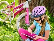 Bikes el casco que lleva de ciclo de la muchacha que mira en la PC de la tableta Imagen de archivo libre de regalías