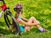 Bikes el casco que lleva de ciclo de la muchacha que se sienta cerca de la bicicleta Fotos de archivo
