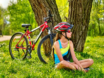 Bikes el casco que lleva de ciclo de la muchacha que se sienta cerca de la bicicleta Imagen de archivo