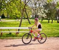 Bikes el montar a caballo de ciclo del casco de la muchacha que lleva en carril de bicicleta Foto de archivo libre de regalías