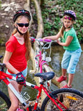 Bikes el vado de ciclo de la muchacha en el agua Foto de archivo