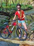 Bikes el vado de ciclo de la muchacha en el agua Fotografía de archivo libre de regalías