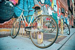Bikes with Graffiti. Two bikes in the sidewalk with colorful graffiti in a wall Royalty Free Stock Photo