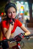 Bikes il casco d'uso della bicicletta della ragazza del ciclista Ritratto all'aperto di notte Fotografie Stock Libere da Diritti