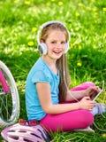 Bikes il casco d'uso di riciclaggio della ragazza che guarda al pc della compressa Fotografie Stock Libere da Diritti
