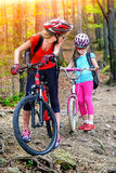 Bikes la famiglia di riciclaggio Biciclette di riciclaggio d'uso del casco della figlia e della madre Fotografie Stock Libere da Diritti