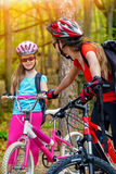 Bikes la famiglia di riciclaggio Il casco d'uso della figlia e della madre sta ciclando sulle biciclette Immagine Stock Libera da Diritti
