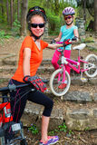 Bikes a la familia Casco que lleva de la madre y de la hija que completa un ciclo en las bicicletas Fotos de archivo