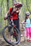 Bikes a la familia de ciclo El casco que lleva de la madre y de la hija está completando un ciclo en las bicicletas Fotos de archivo libres de regalías