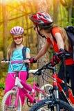 Bikes a la familia de ciclo El casco que lleva de la madre y de la hija está completando un ciclo en las bicicletas Imagen de archivo libre de regalías