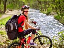 Bikes a la muchacha de ciclo con el vado de ciclo de la mochila grande en el agua en parque Imagen de archivo libre de regalías