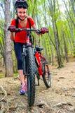 Bikes a la muchacha de ciclo en parque Casco que lleva de la muchacha y mochila grande Fotos de archivo libres de regalías