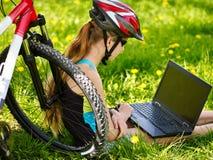 Bikes a la muchacha en el casco de ciclo que se sienta cerca de la bicicleta con el ordenador portátil Imagen de archivo libre de regalías