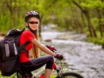 Bikes la ragazza di riciclaggio con guadare di riciclaggio del grande Zaino in tutto l'acqua Fotografia Stock