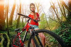 Bikes la ragazza di riciclaggio nel parco Casco d'uso della ragazza e grande zaino Fotografie Stock Libere da Diritti