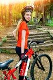 Bikes la ragazza di riciclaggio nel parco Casco d'uso della ragazza e grande zaino Fotografia Stock