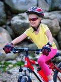 Bikes la ragazza di riciclaggio nel parco La ragazza guida la bicicletta nelle montagne Fotografia Stock