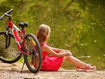 Bikes la ragazza di riciclaggio nel parco La ragazza si siede appoggiandosi la bicicletta sulla riva Fotografie Stock Libere da Diritti