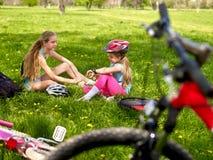 Bikes a las muchachas de ciclo que llevan el casco Las muchachas tienen resto del ciclo Foto de archivo