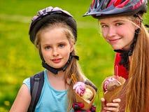 Bikes a las muchachas que completan un ciclo comiendo el cono de helado en parque Foto de archivo libre de regalías