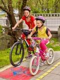 Bikes a muchachas con la mochila que completa un ciclo en carril de la bici Imagen de archivo