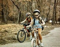 Bikes a muchachas con la mochila que completa un ciclo en la bicicleta Imagen entonada de la sepia Imagenes de archivo