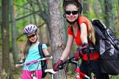 Bikes a muchachas El casco que lleva de la familia feliz está completando un ciclo en las bicicletas Imagenes de archivo