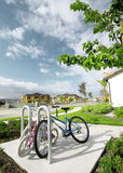 Bikes In Neighborhood. Parked bicycles on the sidewalk in a modern neighborhood housing complex with new homes construction in background.  Blue skies and white Royalty Free Stock Photo