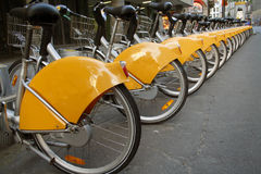 Bikes in a row. A line of colourful rental bikes, parked on the pavement Royalty Free Stock Image