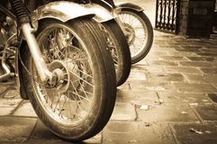 Bikes in a row. Line of the muddy bikes whells in sepia Royalty Free Stock Images