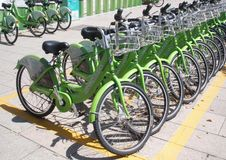 Bikes with shopping baskets for hire. A row of perfectly arranged lime-green bikes with chrome shopping baskets for hire on a sunny day in Zhouzhuang China Stock Images