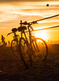Bikes silhouettes and volleyball net on the beach Royalty Free Stock Images