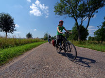 Bikes to Poland. Young girls are riding on the road in the north of Polish in the area of Wegorzewo.n Stock Image
