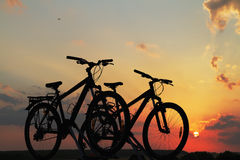 Bikes on top of a car against sunset. Royalty Free Stock Photography