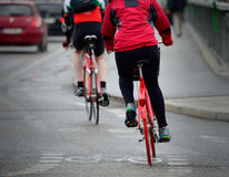 Bikes in traffic. Persons on bikes seen from behind Stock Photo